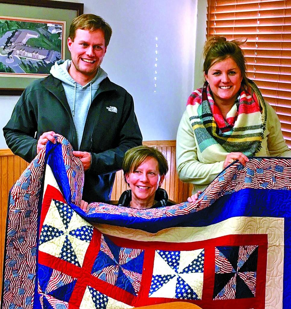 Jake Linder, Sandy Linder, and Bethany Linder accepted a quilt of valor on family member Donald Welle's behalf.
