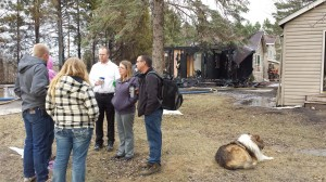 Barrie Hill (backpack) talks with fsmily, friends and neighbors Sunday evening after a fires ravished his home in Rockford Township.