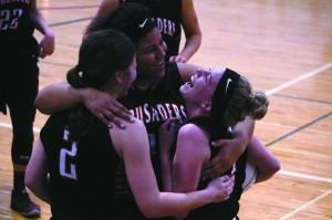 Emilee Gustin is all smiles as she gets congratulated with hugs from teammates Sophie Flucas and Kate Strehlke.