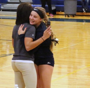 Lanney Lobertmann celebrates her 1,000th career set assist with her coach Brooke Decker.
