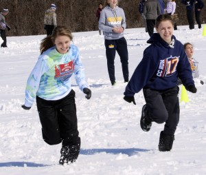 Gwen Helgeson and Gracie Mallak sprint home during the HLWW's track and field Big Base tournament held Tuesday afternoon in the snow.