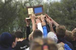 The HLWW boys track and field team hoists their trophy after winning the Section 4A True Team Meet Tuesday evening.