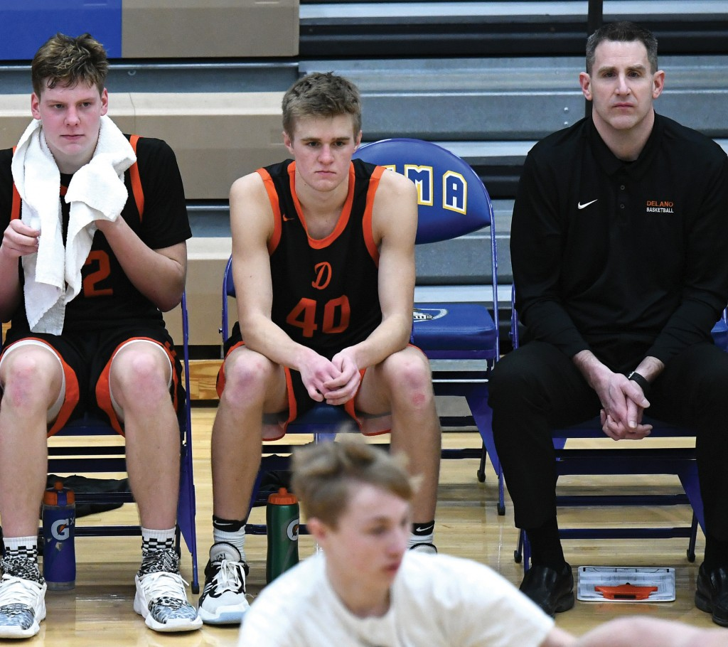 Delano assistant coach Jason Monke waits out the final seconds of Delano's section win over Fridley with seniors Keagen Smith and Jack Balsiger March 12 at St. Michael-Albertville High School. Monke was named to the list of Assistant Coaches of the Year for his work with the Tigers. (Photo by Matt Kane)