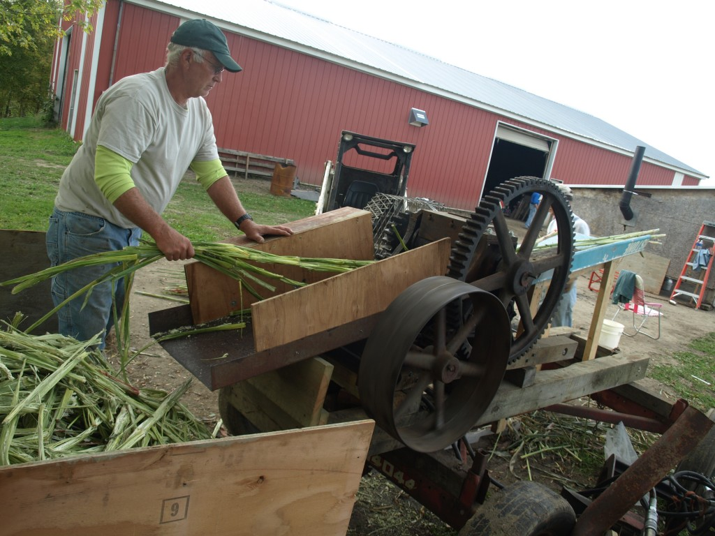 Steve Dahlman uses the sorghum press to squeeze out the sweet liquid from the stalks.