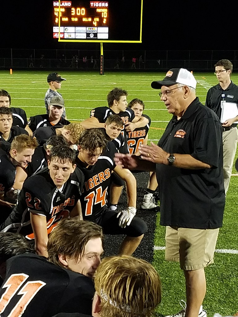 Coach Merrill Pavlovich addresses his players following Delano's 41-10 win over Glencoe-Silver Lake Friday night at Tiger Stadium. The win was Pavlovich's 300th in 43 seasons with the Tigers. Photo by Matt Kane
