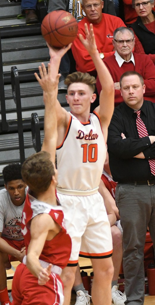 Calvin Wishart strokes his second 3-pointer in the first two minutes of the game in the face of Willmar coach Matt Williams Thursday night. Wishart scored 32 points in the Tigers' 75-54 win. Photo by Matt Kane