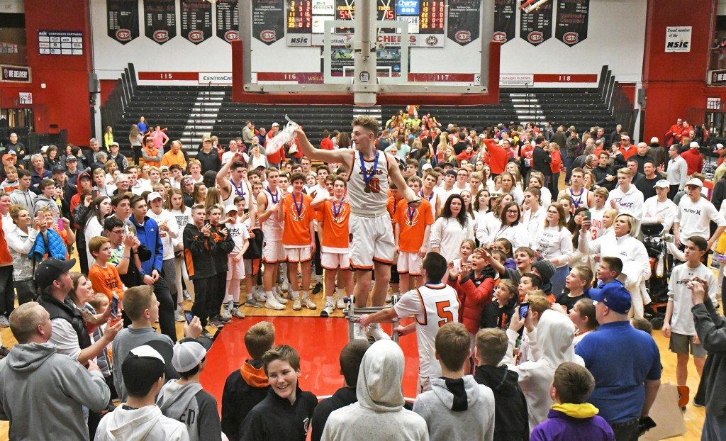 Calvin Wishart shows the Delano crowd the net after freeing it from the rim Thursday night following the Tigers' 75-54 win over Willmar in the Section 5AAA championship game at Halenbeck Hall. Photo by Matt Kane