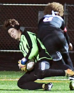 Delano goalkeeper Adam Taylor makes a save with Mayer Lutheran's Lukas Gilbert on his back Tuesday night at Tiger Stadium. Delano won the Section 6A game 4-0, and will play in the quarterfinals Thursday at Mound-Westonka. Photo by Matt Kane