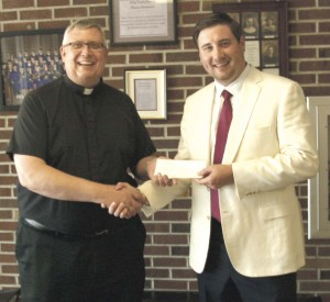 Fr. Tony Stubeda accepted a $3,365 check from 2003 Holy Trinity High School graduate Brenton Hayden.