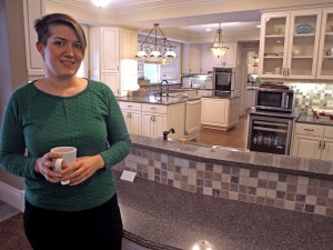 Emily Rieck, director of housing at the Garden House, stands by the spacious kitchen, where residents are welcome to help with meal preparation.