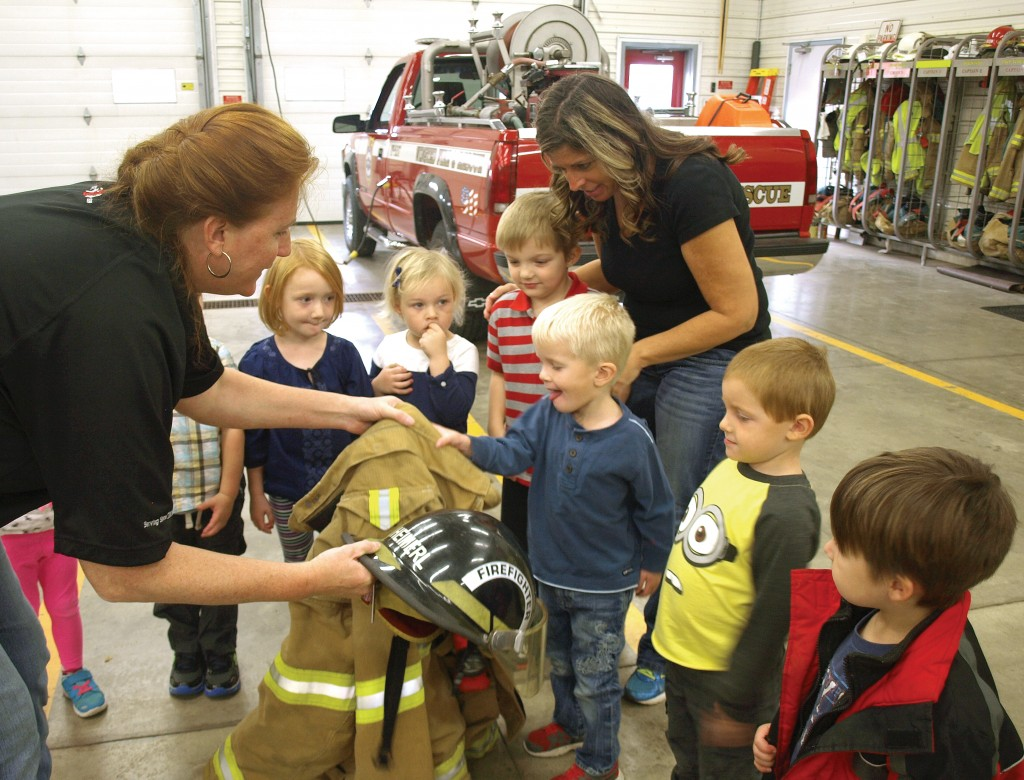 Winsted firefighter Rose Heimerl shows Winsted Elementary preschool students how heavy the jackets are that firefighters wear.