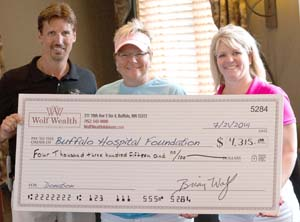 Submitted photo  Brian Wolf of Wolf Wealth Advisors, along with his wife, Debbie (right), presented a big check to Buffalo Hospital Foundation Director Karla Heeter. In addition to money raised through the July 21 charity event, Wolf Wealth Advisors donated extra funds, for a total of $5,000.